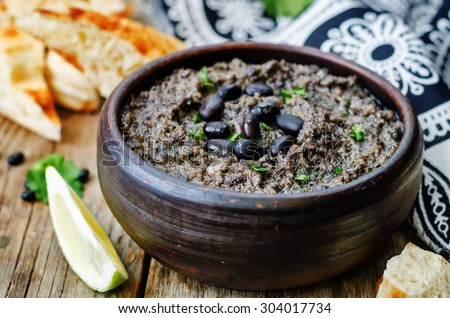 black beans hummus on a dark wood background. the toning. selective focus - stock photo