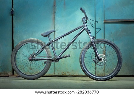 Black bicycle on a green garage background with light effects - stock photo