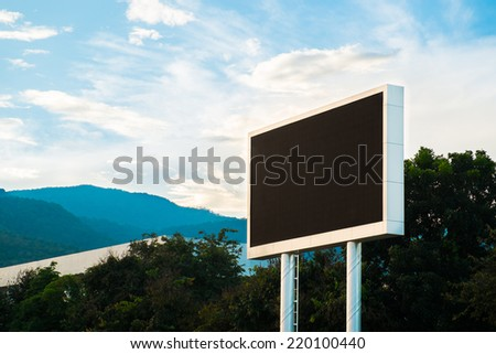 Black billboard with space for your advertisement against blue sky