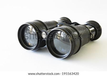 Black binocular lying on a white surface - stock photo