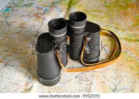 black binoculars on map - stock photo