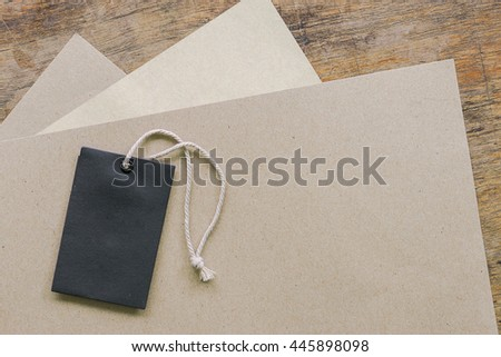 black blank price tag with paper sheet on wood background