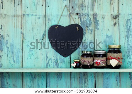 Black blank slate heart hanging on antique rustic teal blue background with jars of fruit jelly on shelf; family and love concept