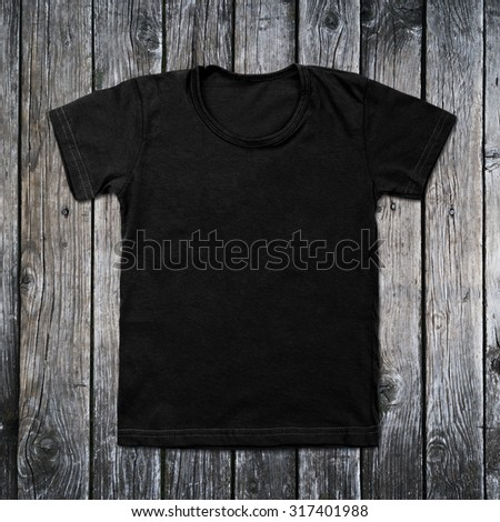Black blank t-shirt on wooden background. - stock photo