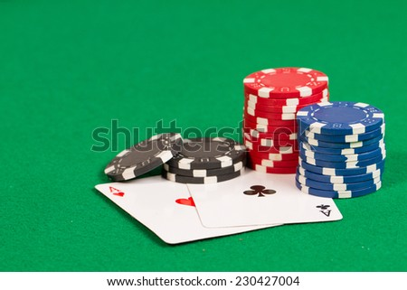 Black, Blue and Red Playing Poker Chips and two aces in a green background - stock photo