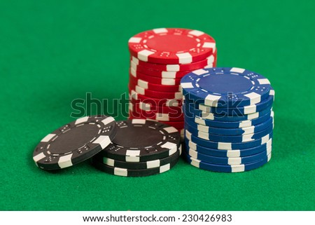 Black, Blue and Red Playing Poker Chips in a green background