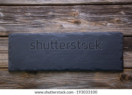 Black board of slate on old rustic wooden background. - stock photo