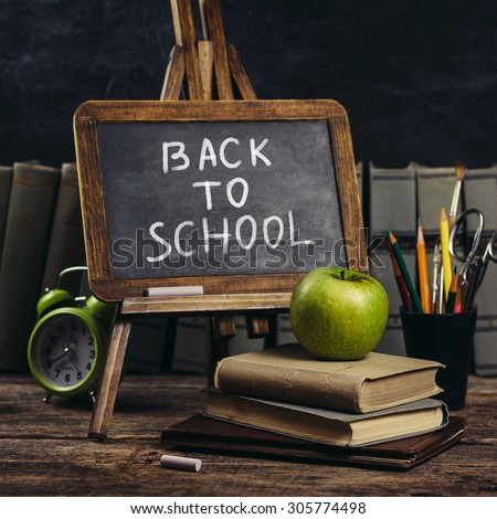 Black board on with text - Back to school. Schoolchild and student studies accessories.