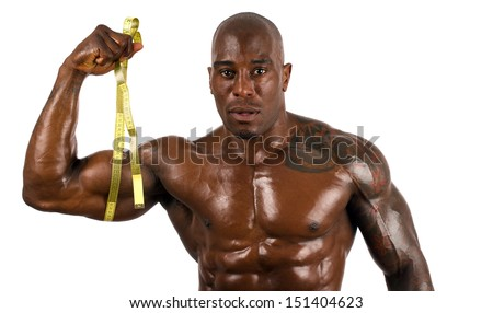 Black bodybuilder taking measurements of his big muscles with a centimeter. Black bodybuilder topless. Strong man with perfect abs, shoulders,biceps, triceps and chest. Isolated on white background