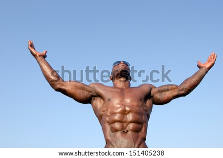 Black bodybuilder wearing sunglasses and showing off his big muscles. Black bodybuilder topless. Strong man with perfect abs, shoulders,biceps, triceps and chest. Isolated on white background