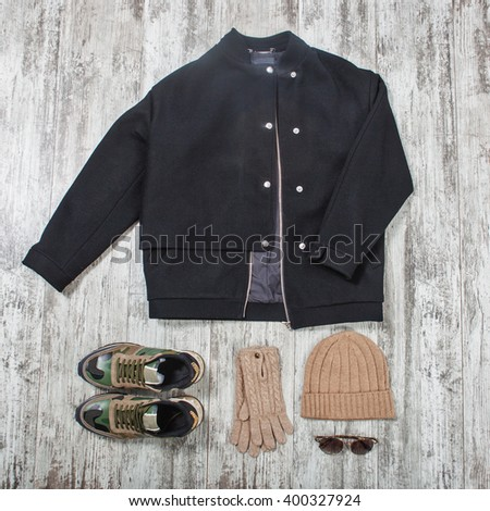 black bomber jacket, sunglasses, beige hat, gloves and military sneakers - stock photo