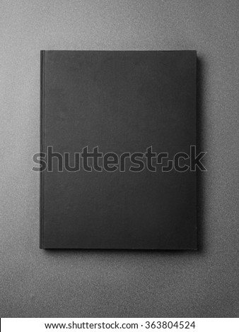 Black book cover on the gray background. - stock photo