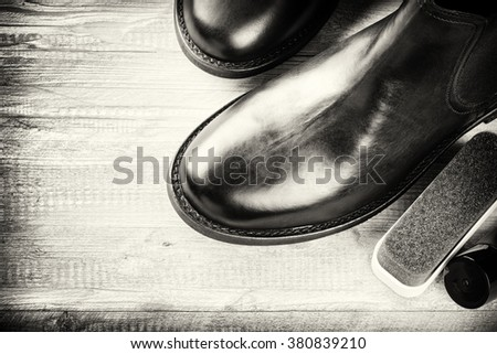 Black boots and shoe care accessories on wooden background. Copy space  - stock photo