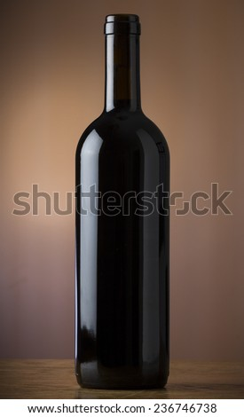 Black bottle of red wine on the background of the canvas - stock photo