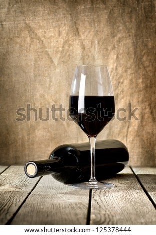 Black bottle of wine and wneglass on the background of the canvas - stock photo