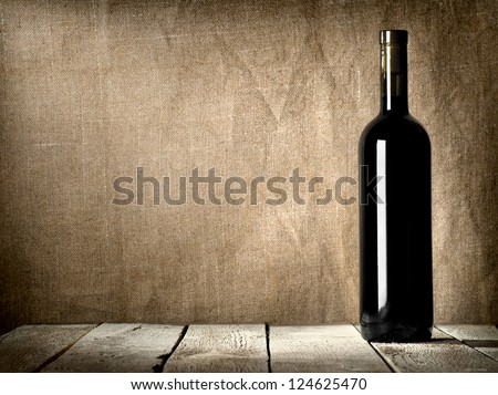 Black bottle of wine on the background of the canvas - stock photo