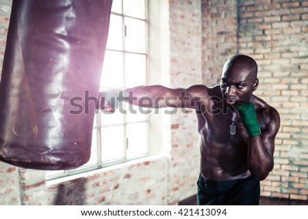 Black boxer punching the heavy bag in the gym - stock photo