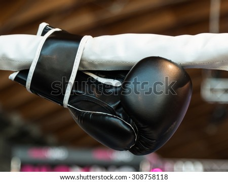 Black Boxing Glove Linked to Ring Ropes - stock photo
