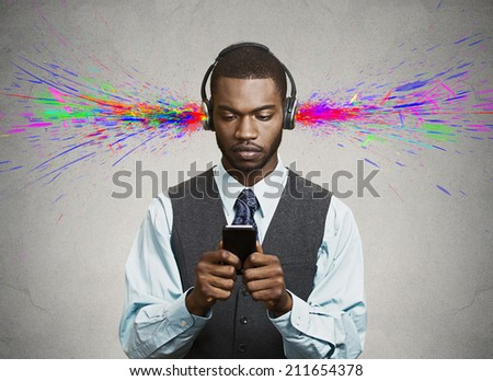 Black boy listening to music with pair of headphones. Closeup portrait young, focused man reading news on smart phone, holding mobile isolated grey wall background. Corporate executive face expression - stock photo
