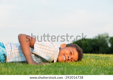 Black boy lying on the grass and smiling.
