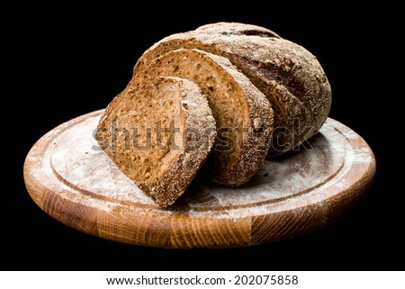 black bread on a board isolated on black background - stock photo