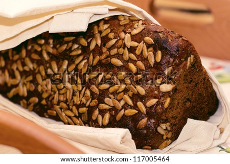Black bread with sunflower seeds wrapped in a towel
