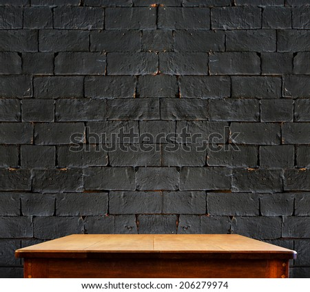 Black brick wall and wooden table,perspective background - stock photo