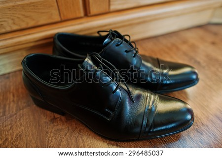 black bridegroom shoes at wooden parquet