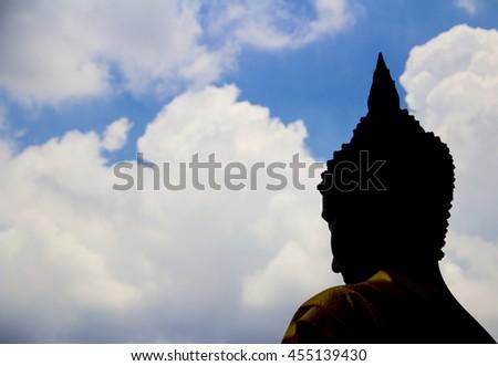 Black buddha silhouette with blue sky - stock photo