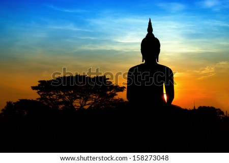 Black buddha silhouette with two tone sky - stock photo