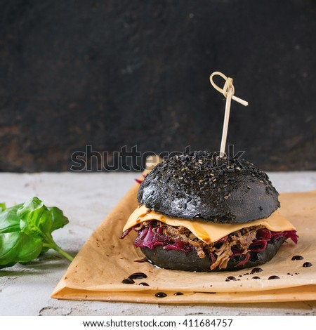 Black burger with beef stews, cheese, red cabbage and balsamic sauce served on baking paper with fresh basil over gray plastered surface with black background. Square image with selective focus