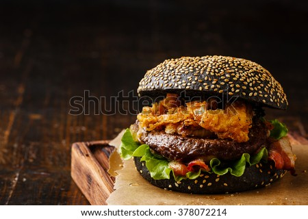 Black burger with sesame seed bun, meat, bacon and onion rings fries on dark wooden background