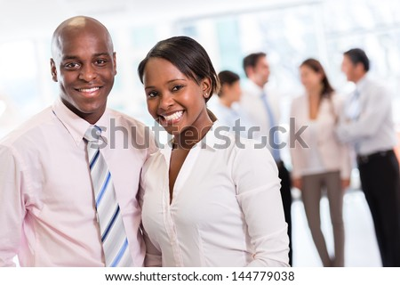 Black business couple looking happy at the office - stock photo