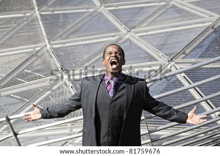 Black business man screaming tired of business network with modern architecture in background. - stock photo