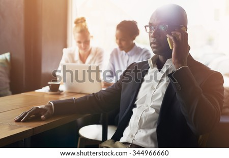 Black business man using cell phone, white and black business woman in background - stock photo