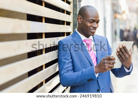 Black business man with a tablet computer in urban background - stock photo