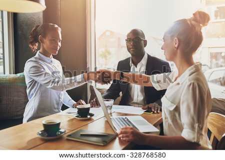 Black business woman and white business woman shaking hands closing a deal - stock photo