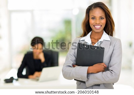black business woman holding clipboard with colleague on background - stock photo