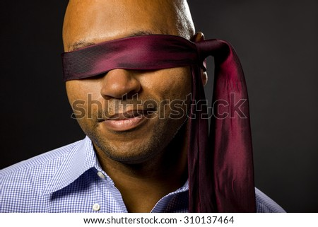 Black businessman blindfolded to represent corporate uncertainty.  The man is disabled by covering his eyes to illustrate vulnerability and employment issues. - stock photo