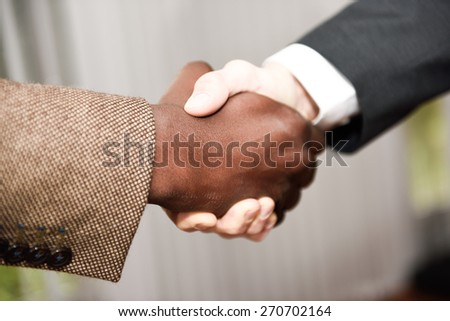 Black businessman shaking hands with a caucasian one wearing suit in a office. Close-up shot - stock photo