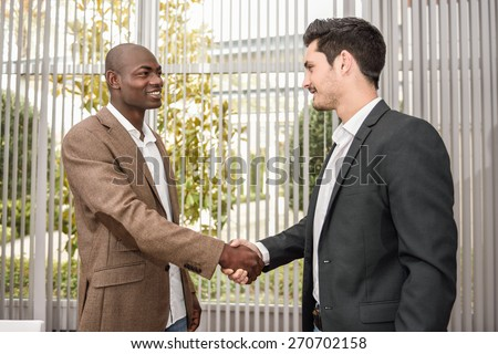 Black businessman shaking hands with a caucasian one wearing suit in a office. Two men smiling - stock photo