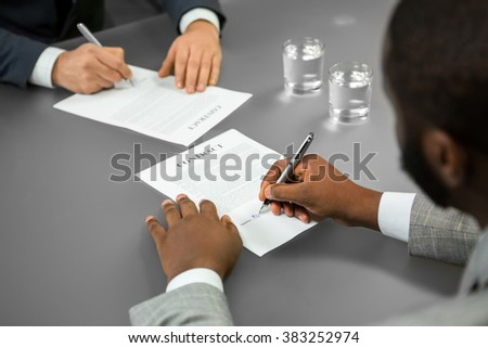 Black businessman signs a contract. Welcome to the company. Chief employs manager. A successful candidate. - stock photo