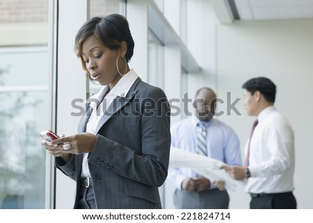 Black businesswoman text messaging on cell phone - stock photo