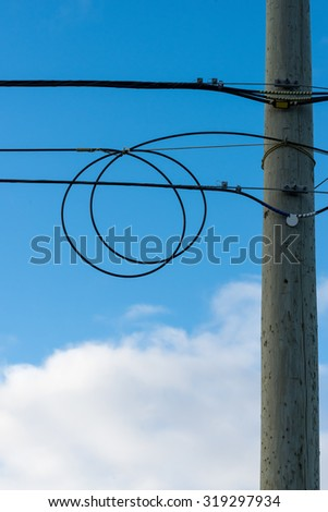 Black cable with a loop hanging on post - stock photo
