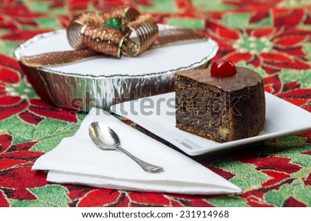 black cake, typical of Latin America regions at Christmas time, and placed on a tablecloth with Christmas decorations - stock photo