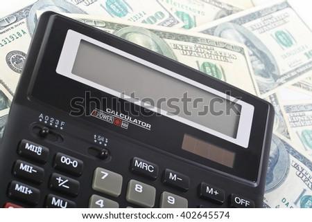 black calculator on hundred dollar banknotes - stock photo