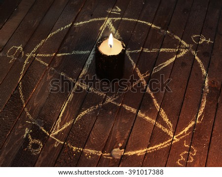 Black candle in pentagram on wooden planks. Magic ritual with occult, evil and esoteric symbols. Scary halloween rite - stock photo