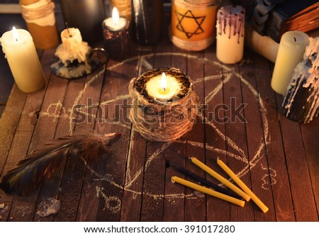 Black candle in the circle with pentagram and magic candles on old table. Black magic ritual with occult, evil and esoteric symbols. Scary halloween rite - stock photo