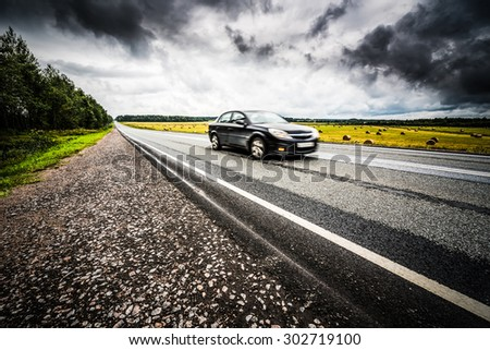 Black car racing on a rural road. View from the side of the road, image vignetting and hard tones - stock photo