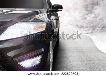 black car without a trade brand and gray road with landscape of snow  - stock photo